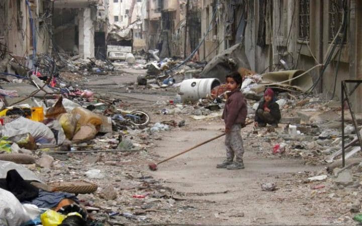 A child clears damage and debris in the besieged area of Homs