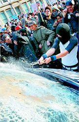 Ενας διαδηλωτής σπάει το τζάµι ενός αυτοκινήτου της Αστυνοµίας, κατά τα  επεισόδια που σηµάδεψαν τη χθεσινή φοιτητική διαδήλωση στο Λονδίνο