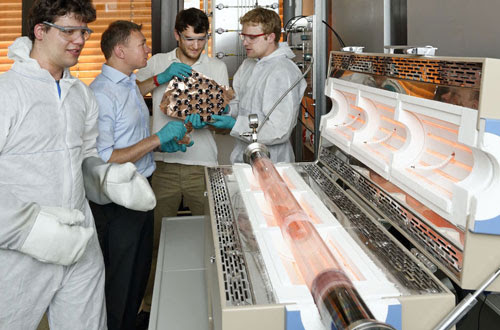 from left to right: Luca Banszerus, Christoph Stampfer, Michael Schmitz and Stephan Engels standing by the chemical vapour deposition oven in their laboratory