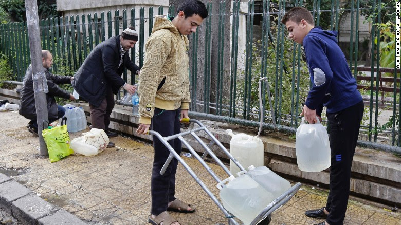 Syrians fill plastic containers with water at a public fountain by a park in Damascus.