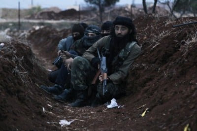 Members of al Qaeda's Nusra Front carry their weapons as they sit  in a trench near al-Zahra village, north of Aleppo city