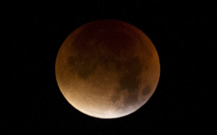 The Moon, appearing a dim red colour, is covered by the Earth's shadow during a total lunar eclipse over Dover in southern England