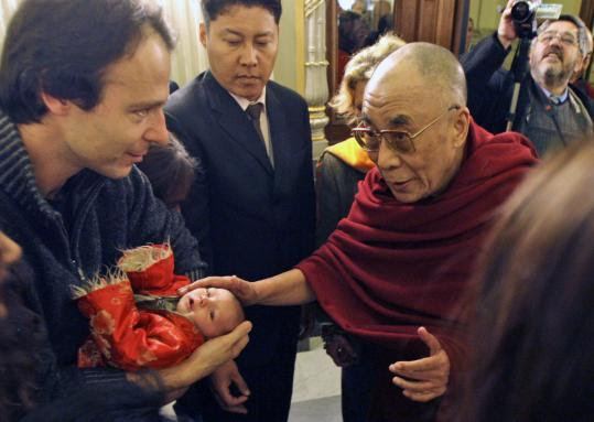 The Dalai Lama blessed a child yesterday upon his arrival in Prague for a meeting with former president Václav Havel. He also had plans to address the Tibet Group in the Czech Parliament.