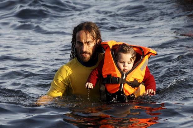Voluntário carrega bebê que estava em barco com 150 refugiados que virou nesta sexta-feira (30) (Foto: Giorgos Moutafis/Reuters)