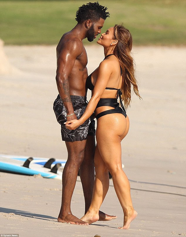 Beach kisses:She had on a skimpy black bathing suit and had both her hair and makeup done to perfection as she showed off her bikini body while walking down the beach
