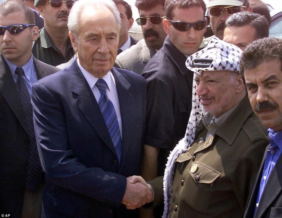 Histórico: Shimon Peres é retratado (à esquerda) agitando as mãos com o líder palestino Yasser Arafat em 2001. Peres, Arafat eo terceiro vencedor do Prémio Nobel da Paz Yitzhak Rabin estão todos mortos agora.  Rabin foi assassinado por um colono judeu irritado com os acordos de paz de Oslo tinham acordado