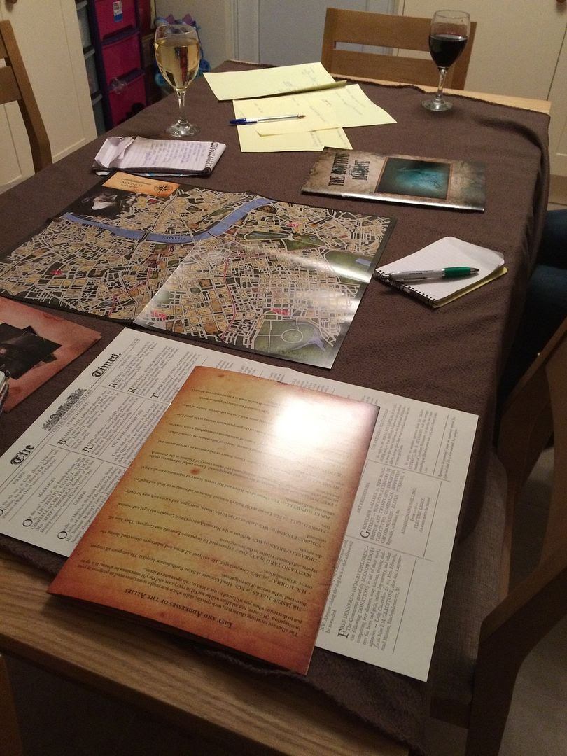 A game of Sherlock Holmes Consulting Detective in progress, with copious notes and maps spread out across a kitchen table with glasses of wine.