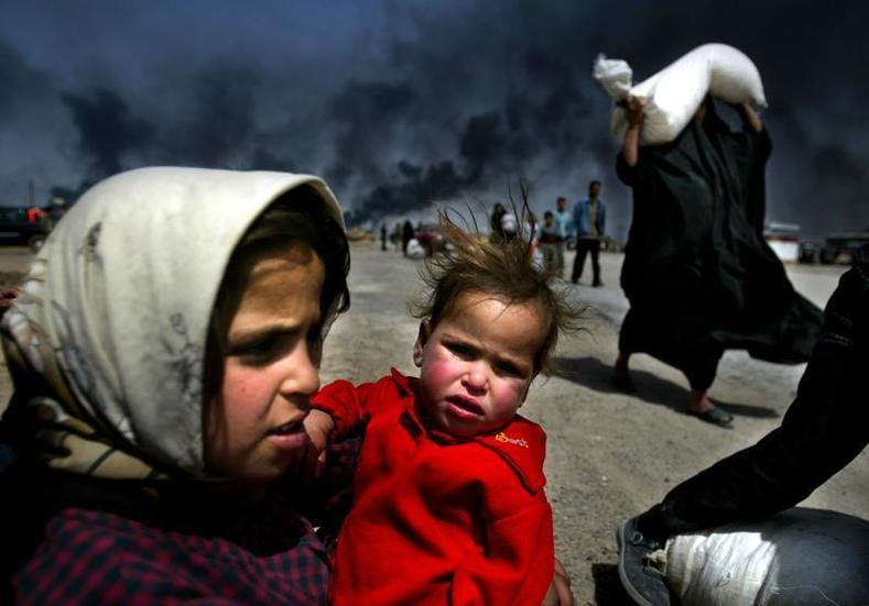 An Iraqi girl holds her sister as she waits for her mother (R) to bring over food bought in Basra March 29, 2003.