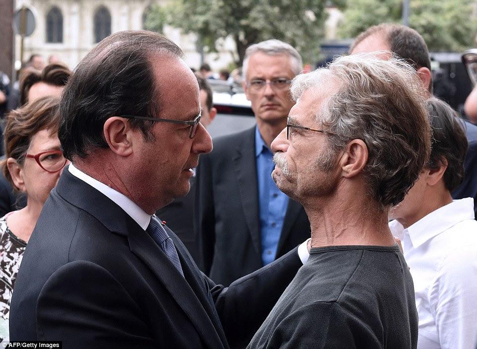 """O presidente francês, François Hollande (foto abraçando o prefeito da cidade Hubert Wulfranc) disse que a França está """"em guerra"""" com ISIS enquanto o grupo terrorista assumiu a responsabilidade pela morte"""