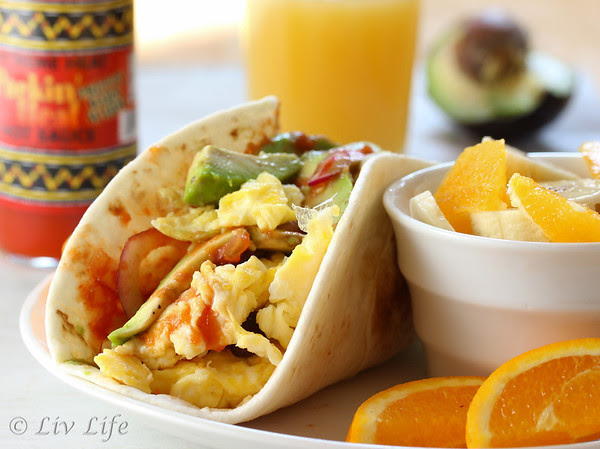 Breakfast Taco with eggs and avocado pictured with fruit