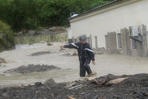 A Taiwanese man wades through a flash flood triggered by typhoon Nanmadol in Manchu, Pingtung County, Southern Taiwan, Monday, Aug. 29, 2011. Nanmadol slammed into Taiwan, closing schools, workplaces