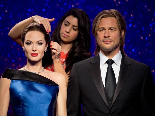 A cabeleireira Caryn Bloom acerta últimos detalhtes das novas estátuas de cera do casal Angelina Jolie e Brad Pitt  do museu londrino Madame Tussauds, em evento nesta terça-feira (17) (Foto: Leon Neal/AFP)