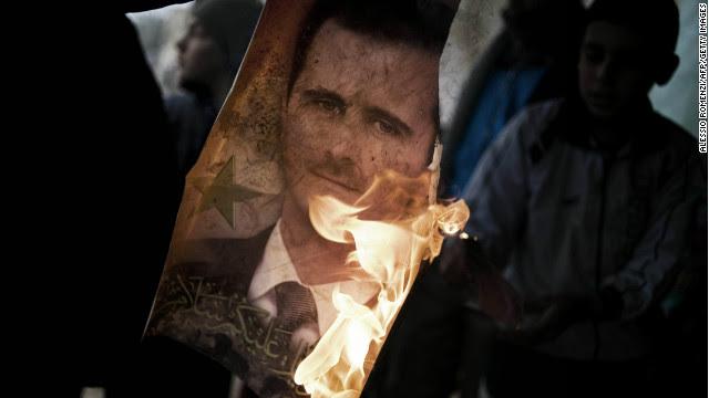 Member of Free Syrian Army holds burning portrait of President Bashar al-Assad in Al-Qsair, January 25, 2012.