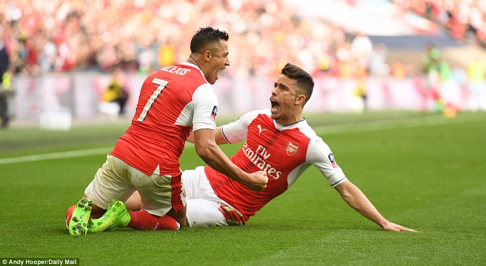 Sanchez and Gunners team-mate Gabriel slide on the Wembley turf as the post-goal celebrations continue