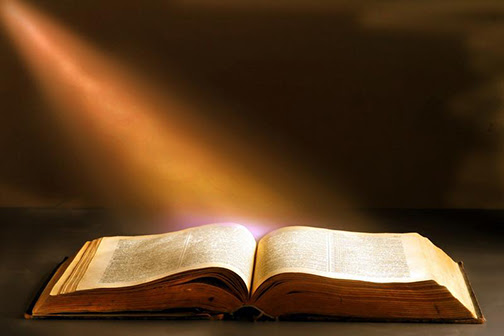 [Photo of a sunbeam falling on an open Bible]
