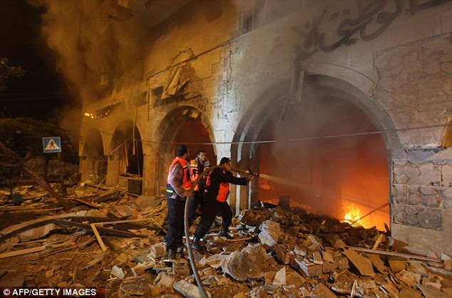 Battle: Palestinian firefighters try to extinguish a blaze after an Israeli air strike on the Islamic National Bank building in Gaza City