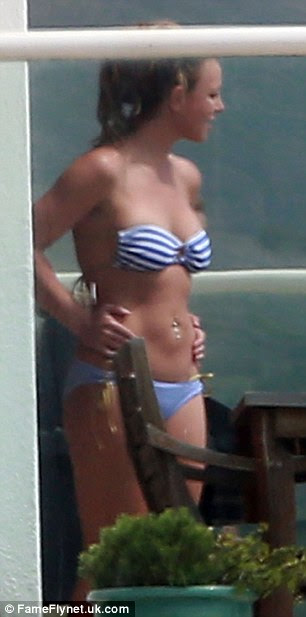 Working on her tan: Spears enjoyed a cigarette break as she lapped up the rays in her friend's house