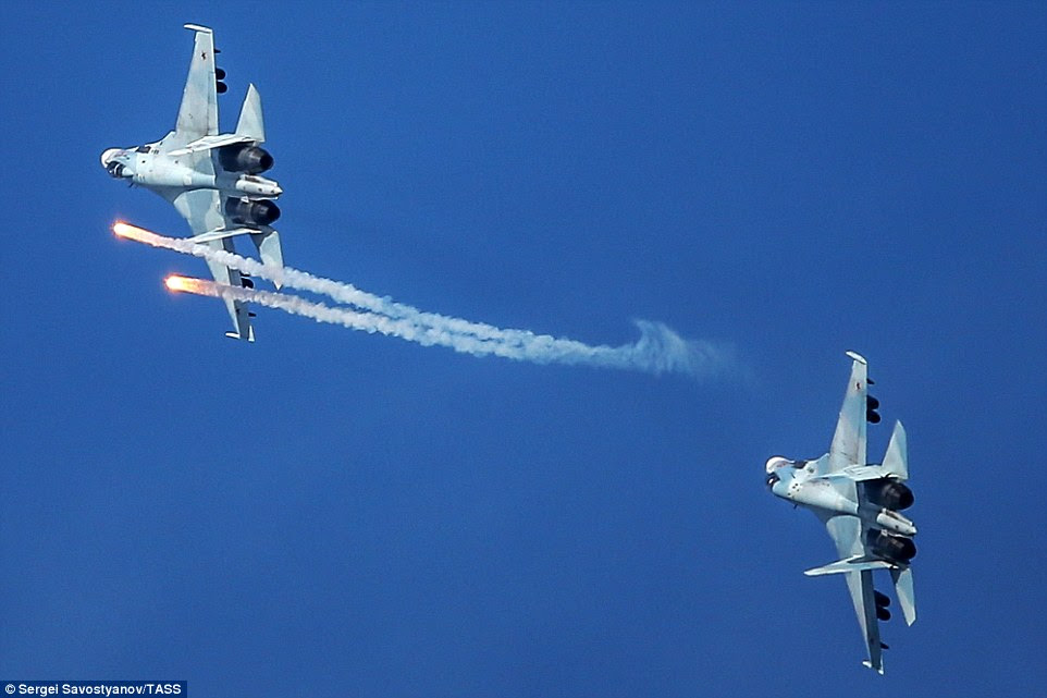 Two Sukhoi Su-35 multi-role fighters fly in formation as one fires off two missiles through the clear blue sky. Friday's drills took place in hot, sunny weather