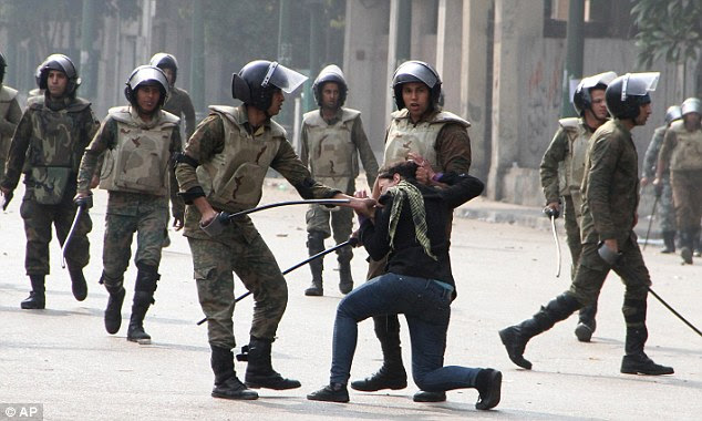 Violent: Egyptian army soldiers use brutal force to arrest this female protester and drag her by her hair during clashes with military police near Cairo's Tahrir Square