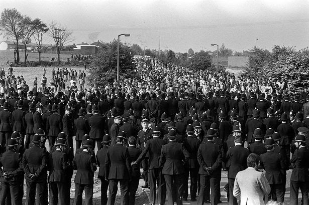 http://i3.mirror.co.uk/incoming/article1393689.ece/ALTERNATES/s615/Police+greeting+pickets+as+they+arrive+on+the+hill+heading+to+the+Orgreave+Coking+Plant+near+Rotherham