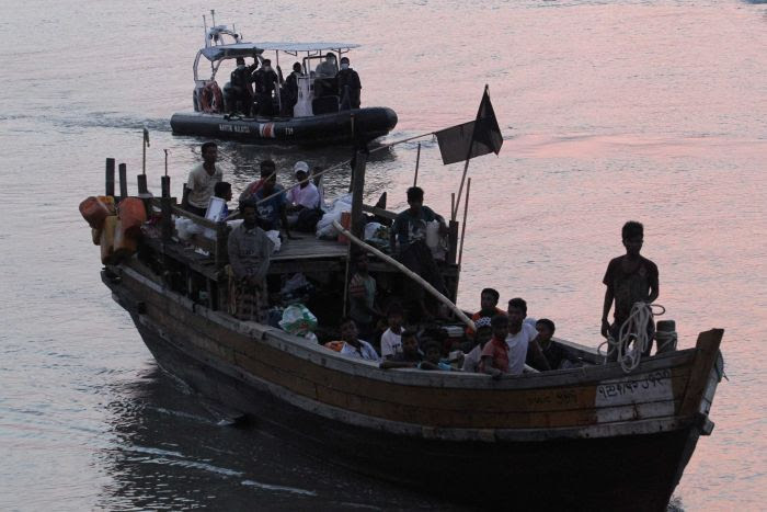 Rohingya refugees sit on a boat on the water at dusk.