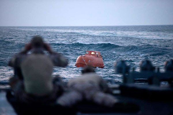 From the stern of the USS Bainbridge, Navy SEAL snipers monitor a lifeboat carrying Captain Richard Phillips and four Somali pirates holding him hostage in CAPTAIN PHILLIPS.