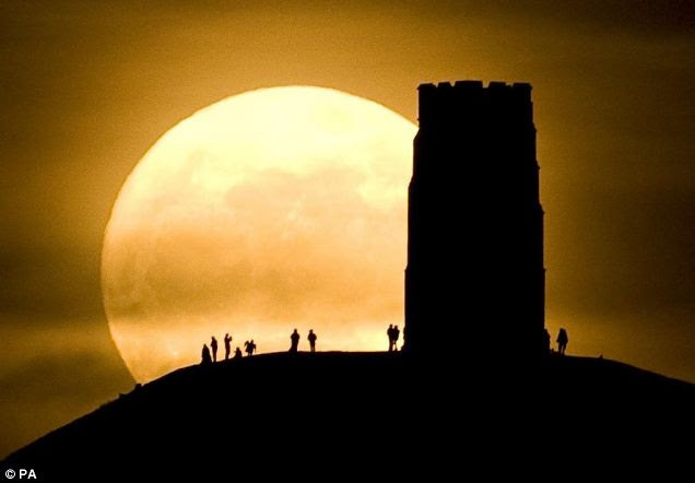 Revellers stand beside St. Michael's Tower on Glastonbury Tor watching the moon as it is at its closest point to the Earth for almost two decades