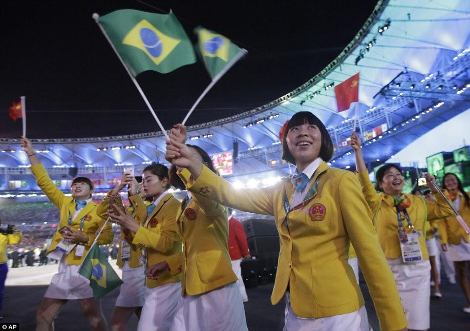 Equipe China caminha na arena durante a cerimônia de abertura dos Jogos Olímpicos de 2016 no Rio de Janeiro acenando as bandeiras brasileiras e chinesas