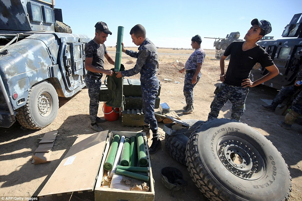 Pictured, policemen yesterday inspect the weapons before the movement. The militias have regained much of the territory lost to ISIS in 2014 and 2015
