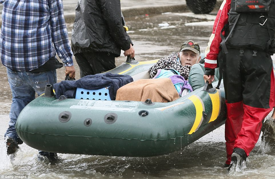 A man is carried out of flood water in a rubber boat after being rescued by volunteers in Corpus Christi