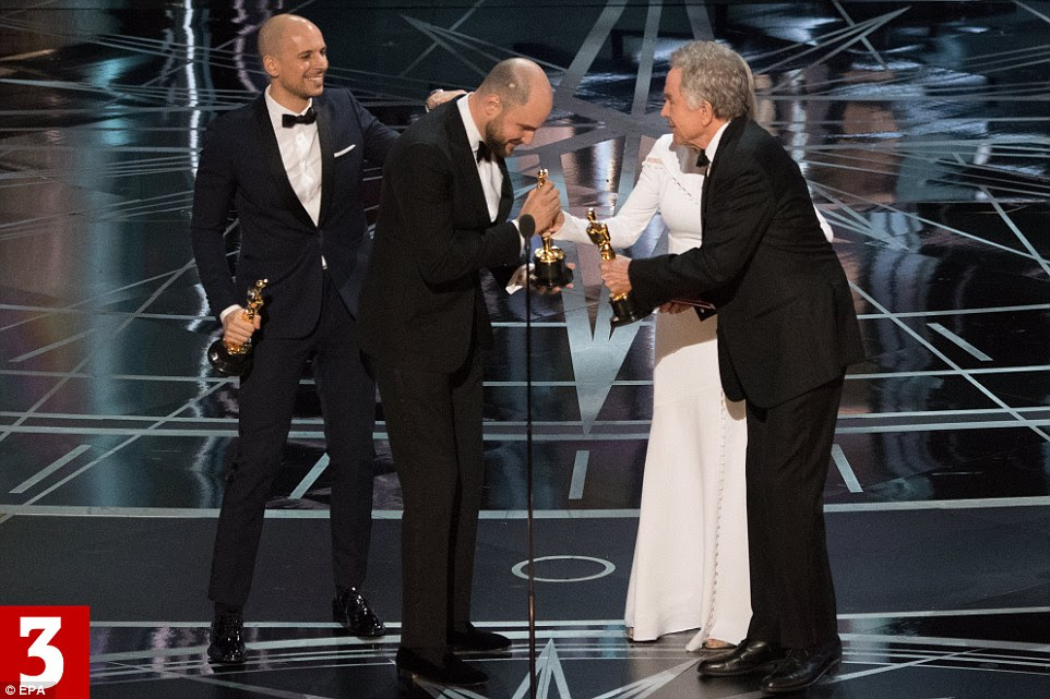La La Land producers Jordan Horowitz and Fred Berger (left) arrive on stage to accept the award from Dunaway and Beatty as the cast and crew follow suit