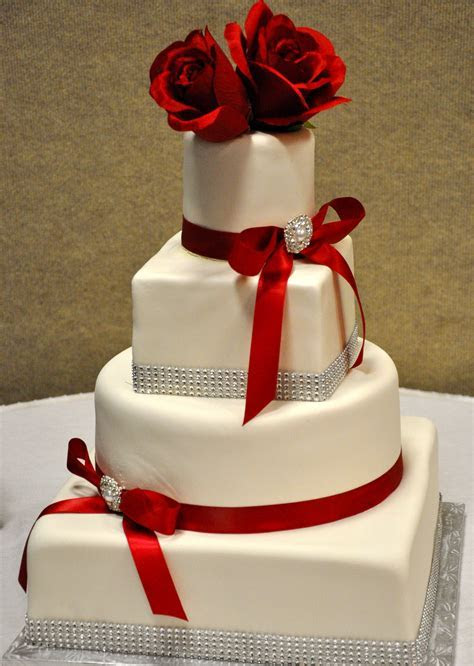 Three tier wedding cake with red flowers and red ribbon #
