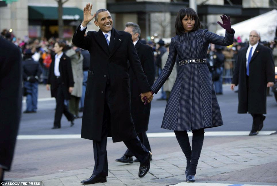 Taking a stroll: The Obamas wave to the crowds gathered along the parade route following the inauguration ceremony