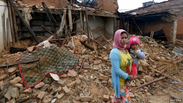 A Nepali woman holds her baby in front of the wreckage of a house that was completely destroyed in Saturday's earthquake in Gorkha, Nepal (30 April 2015)