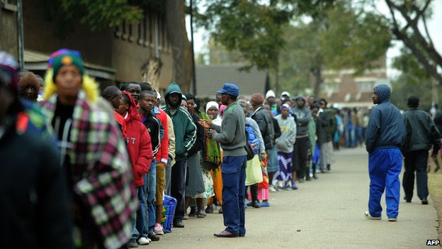 Zimbabweans line up near a polling station in Harare to vote in a general election on 31 July 2013