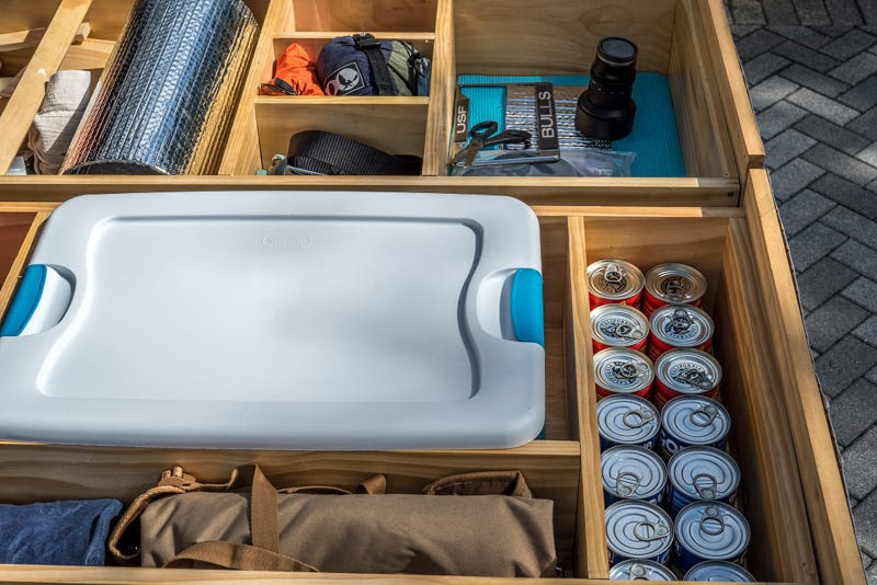 The drawers underneath the memory foam mattress hold his camping gear, food, and other supplies.