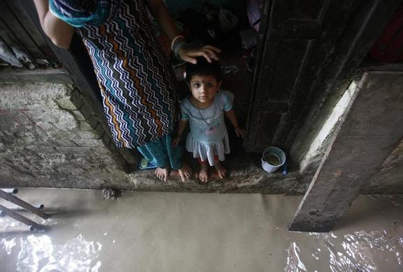A child watches while standing on the doorstep of her house next to a flooded alley due to rising water level of river Yamuna after heavy monsoon rains in New Delhi, June 18, 2013. . REUTERS-Anindito Mukherjee