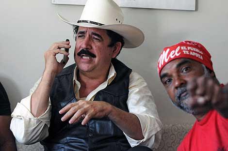 Manuel Zelaya (izquierda), en la embajada de Brasil, junto a un seguidor. | Afp