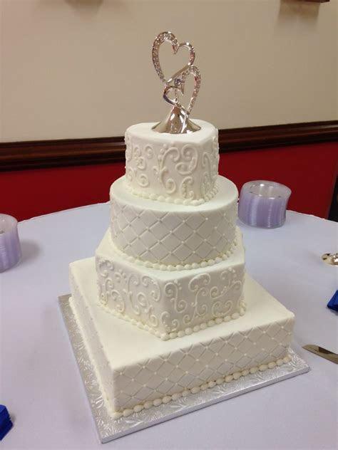 Four tier buttercream wedding cake with square, hexagon