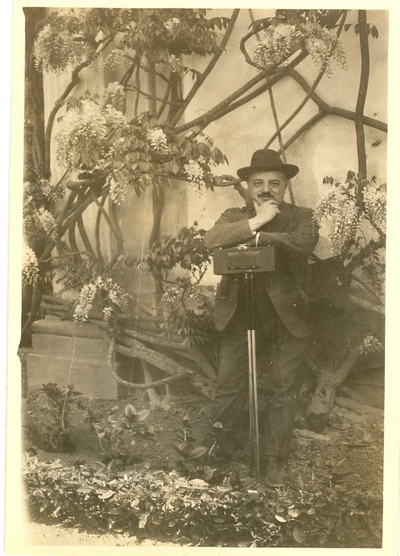 Retrato de José Regueira con su cámara Kodak Panoram 4 junto a una glicinia