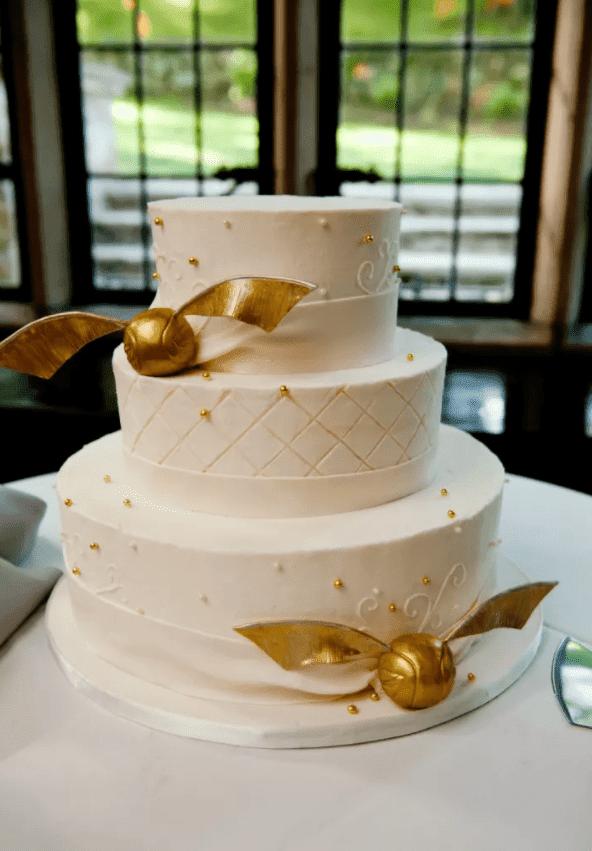 eine schicke Hochzeitstorte in weiß mit gold Perlen und gold snitches