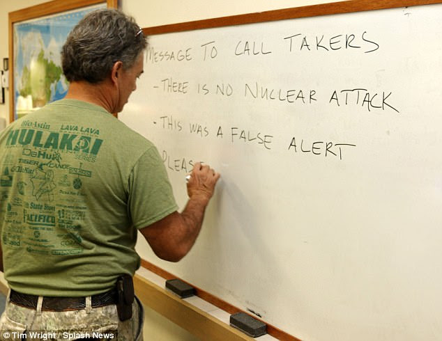 A Hawaii Civil Defense official is seen above on Saturday writing instructions for dispatchers fielding calls from terrified locals