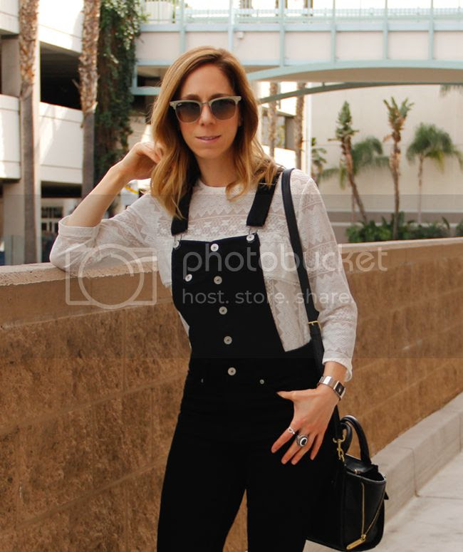 Fashion blogger The Key To Chic wears a white lace blouse with black overalls and Topshop leopard print ankle boots.