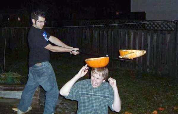 33 - pic of man slicking pumpkin off another man's head.