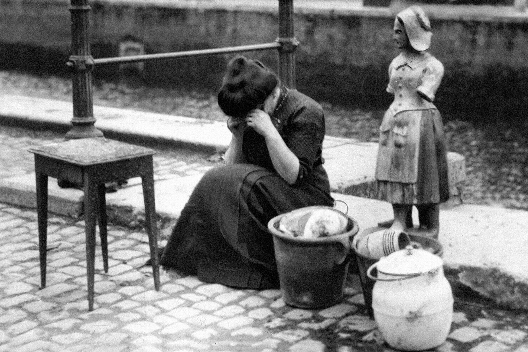 A woman weeps at the roadside beside a table some pots and pans and a heavy stone statue her worldly treasures