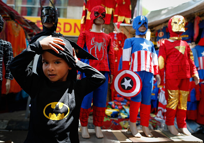 Weekend Pictures: Kuala Lumpur, Malaysia: A boy tries on Batman's costume before Eid al-Fitr