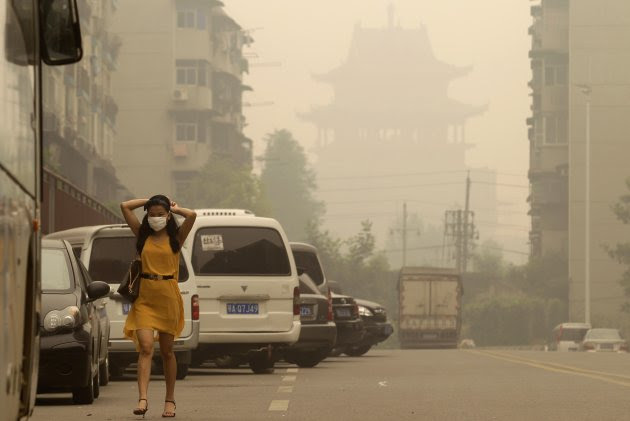 A woman wears a mask as she walks along a street in front of a Chinese temple during a hazy day in Wuhan, Hubei province June 11, 2012. China's carbon emissions could be nearly 20 percent higher than previously thought, a new analysis of official Chinese data showed on Sunday, suggesting the pace of global climate change could be even faster than currently predicted. REUTERS/Stringer (CHINA - Tags: ENVIRONMENT) CHINA OUT. NO COMMERCIAL OR EDITORIAL SALES IN CHINA