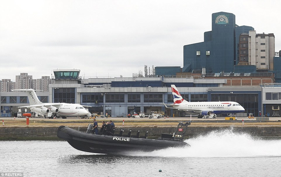 A police dingy is pictured sailing past aircraft at the airport as the protest closed the runway and caused flights to be delayed
