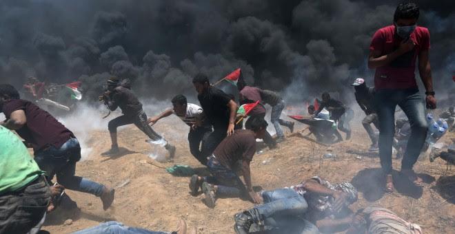 Un grupo de palestinos huyen y se tiran al suelo ante el fuego israelí en Gaza. /REUTERS