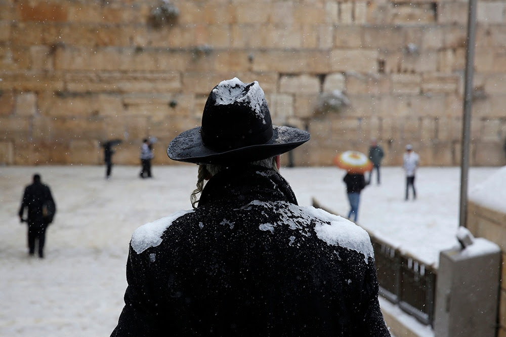 A man stands in front of the Western Wall as snow falls in Jerusalem's Old City. (REUTERS/Darren Whiteside)